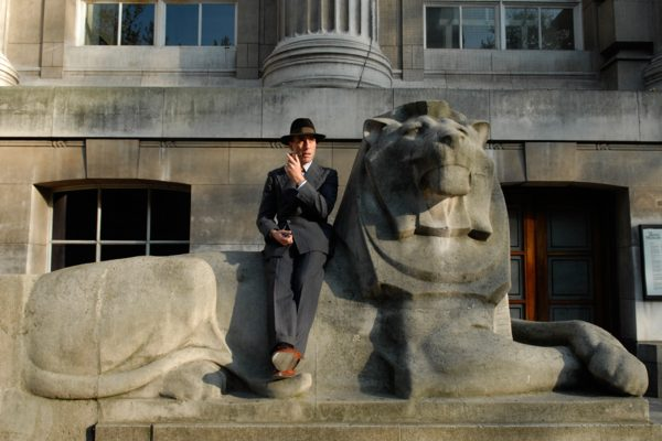 man with pipe and hat sitting on a carving of a stone lion smoking a pipe outside the British Museum